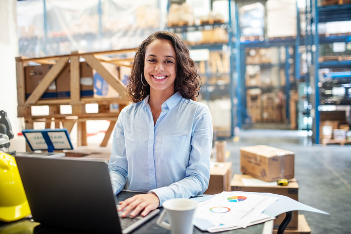 Businesswoman with a laptop working at warehouse